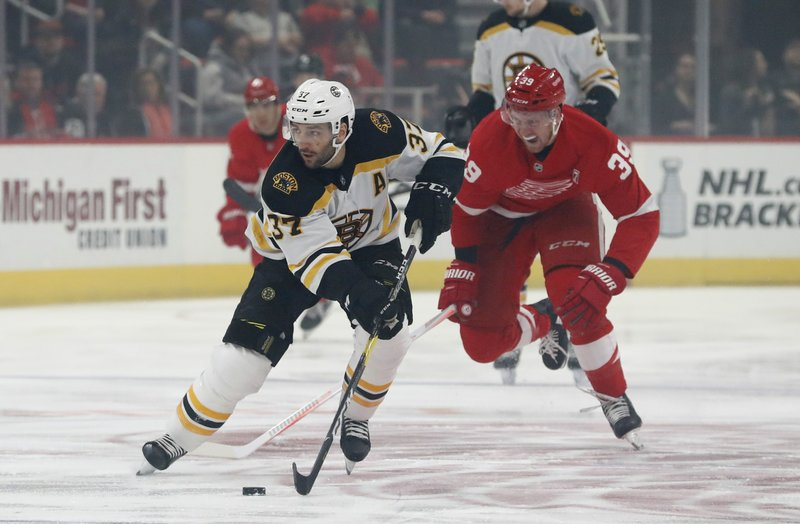 Boston Bruins center Patrice Bergeron (37) controls the puck as Detroit Red Wings right wing Anthony Mantha (39) chases during the first period of an NHL hockey game, Sunday, March 31, 2019, in Detroit. (AP Photo/Carlos Osorio)