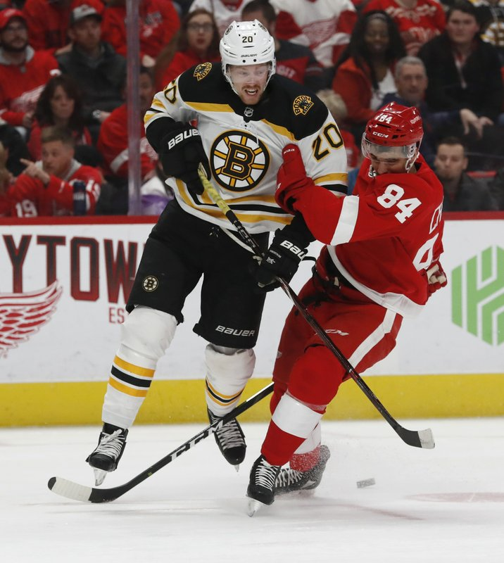Boston Bruins center Joakim Nordstrom (20) and Detroit Red Wings defenseman Jake Chelios (84) check each other during the first period of an NHL hockey game, Sunday, March 31, 2019, in Detroit. (AP Photo/Carlos Osorio)