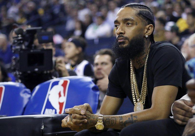 FILE - In this March 29, 2018, file photo, rapper Nipsey Hussle watches an NBA basketball game between the Golden State Warriors and the Milwaukee Bucks in Oakland, Calif. (AP Photo/Marcio Jose Sanchez, File)