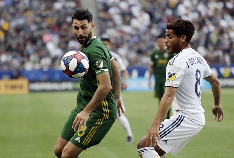 Portland Timbers midfielder Diego Valeri, left, controls the ball next to Los Angeles Galaxy midfielder Jonathan dos Santos, right, during the first half of an MLS soccer match Sunday, March 31, 2019, in Carson, Calif. (AP Photo/Marcio Jose Sanchez)