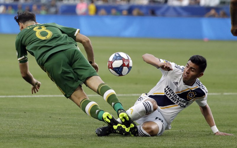 Los Angeles Galaxy midfielder Joe Corona, right, defends on Portland Timbers midfielder Diego Valeri, left, during the first half of an MLS soccer match Sunday, March 31, 2019, in Carson, Calif. (AP Photo/Marcio Jose Sanchez)