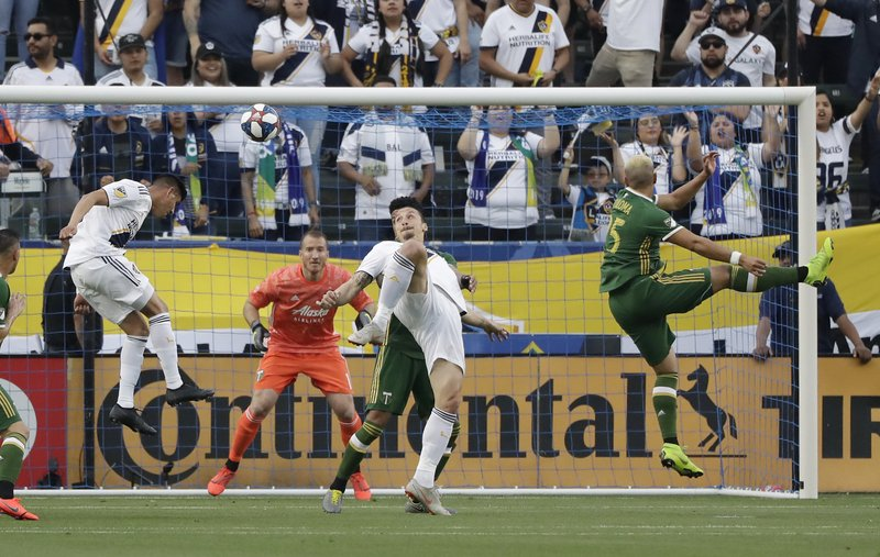 Los Angeles Galaxy's Joe Corona, left, heads the ball next to teammate Zlatan Ibrahimovic and Portland Timbers defender Bill Tuiloma, right, during the first half of an MLS soccer match Sunday, March 31, 2019, in Carson, Calif. (AP Photo/Marcio Jose Sanchez)
