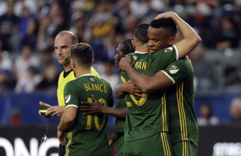 Portland Timbers forward Jeremy Ebobisse, right, hugs teammate David Guzman after Ebobisse's goal against the Los Angeles Galaxy during the first half of an MLS soccer match Sunday, March 31, 2019, in Carson, Calif. (AP Photo/Marcio Jose Sanchez)