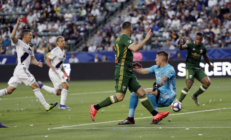 Portland Timbers midfielder David Guzman, center, passes the ball past Los Angeles Galaxy goalkeeper David Bingham, in blue, to assist on a goal by forward Jeremy Ebobisse, right, during the first half of an MLS soccer match Sunday, March 31, 2019, in Carson, Calif. (AP Photo/Marcio Jose Sanchez)