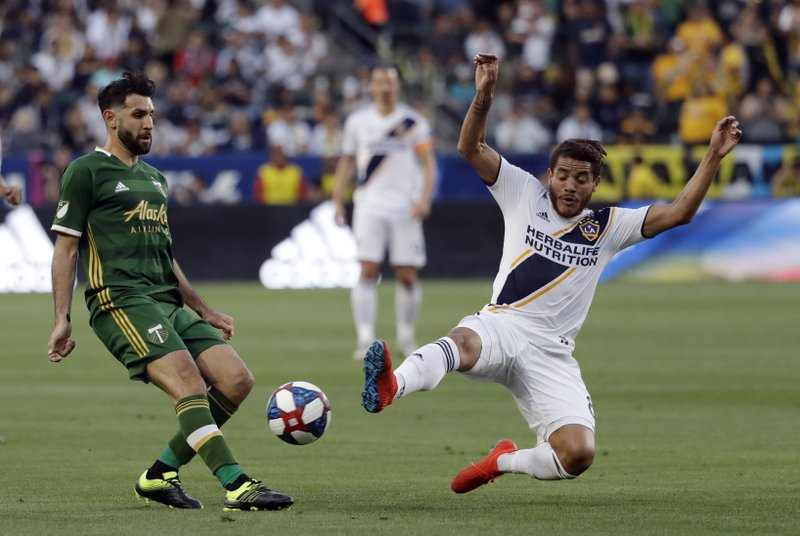 Portland Timbers midfielder Diego Valeri, left, shoots as Los Angeles Galaxy midfielder Jonathan dos Santos, right, defends during the first half of an MLS soccer match Sunday, March 31, 2019, in Carson, Calif. (AP Photo/Marcio Jose Sanchez)