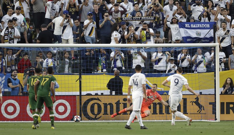 Los Angeles Galaxy forward Zlatan Ibrahimovic (9) scores on a penalty kick past Portland Timbers goalkeeper Jeff Attinella, in orange, during the first half of an MLS soccer match Sunday, March 31, 2019, in Carson, Calif. (AP Photo/Marcio Jose Sanchez)