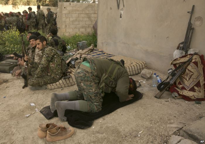 A U.S.-backed Syrian Democratic Forces fighter prays after returning from the