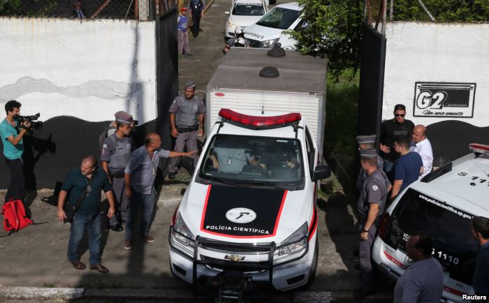 A vehicle of the forensic team leaves the Raul Brasil school after a shooting