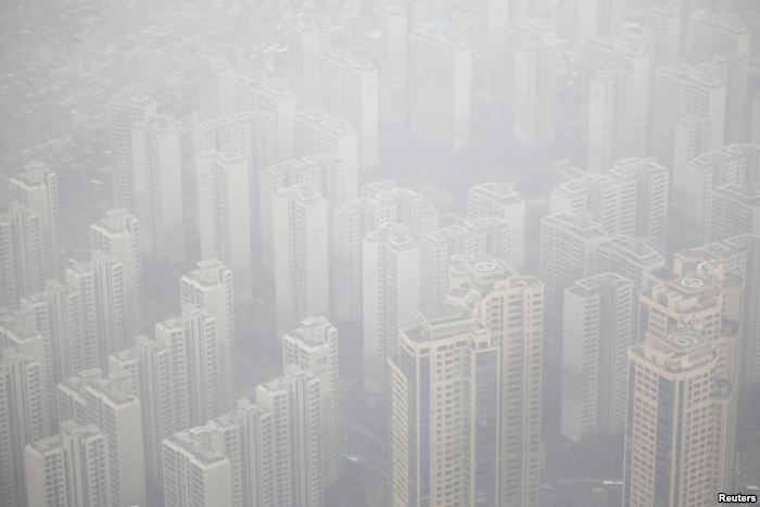 Apartment complexes are seen shrouded by fine dust during a polluted day in S