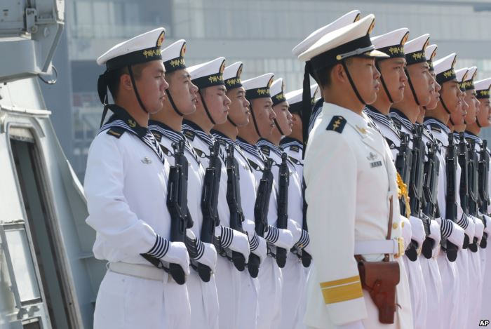 Chinese People's Liberation Army Navy troops stand in formation on the de