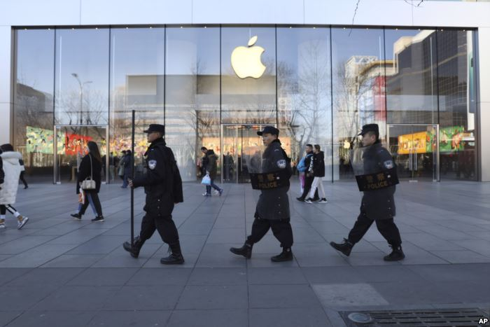 Chinese security guards march past an Apple store in Beijing, China, March 6,