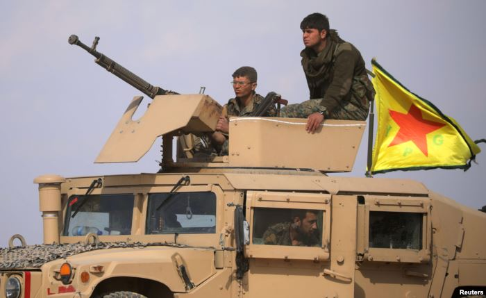 Fighters from the Syrian Democratic Forces are seen on a military vehicle nea