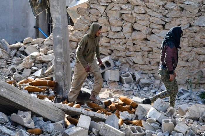 Fighters of the US-backed Kurdish-led Syrian Democratic Forces walk through d
