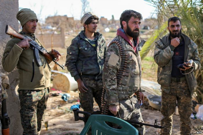 Fighters with the U.S.-backed Syrian Democratic Forces (SDF) check a makeshif