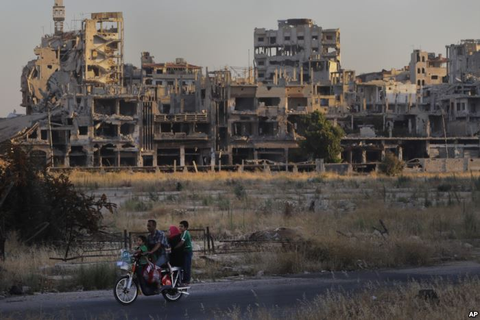 FILE - People ride their motorcycle by damaged buildings in the old town of H