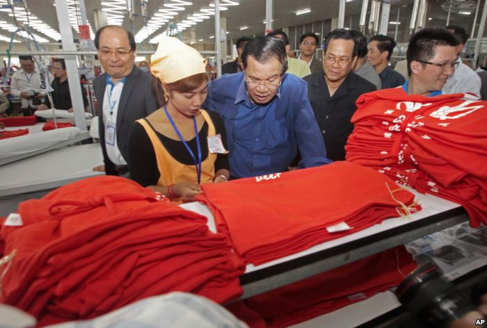 FILE - Prime Minister Hun Sen, center, leans over a garment worker during a v