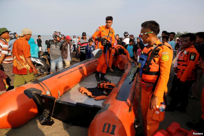FILE - Rescue team members prepare the boat heading to the location of Lion A