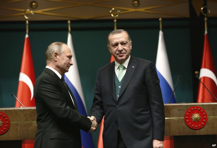 FILE - Turkey's President Recep Tayyip Erdogan, right, shakes hands with