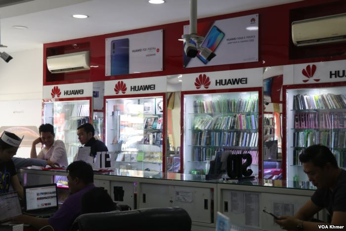 Huawei logos and products are seen advertised at a local phone shop, in Phnom