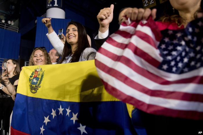 Members of the audience wave Venezuelan and American flags as President Donal