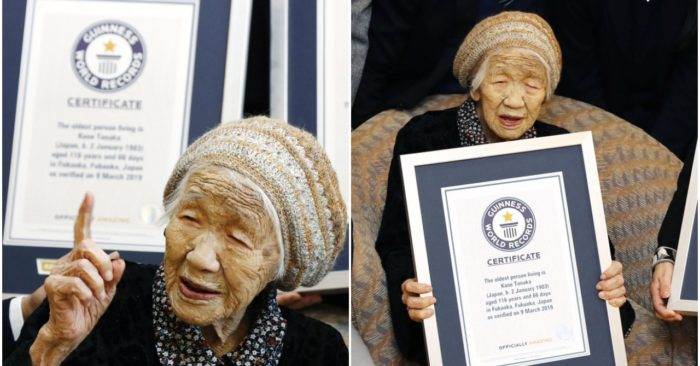 Kane Tanaka, a 116-year-old Japanese woman, gestures after receiving a Guinness World Records certificate, back, at a nursing home where she lives in Fukuoka, southwestern Japan, Saturday, March 9, 2019. Tanaka who loves playing the board game Othello was honored Saturday as the world's oldest living person by Guinness World Records. (Takuto Kaneko/Kyodo News via AP)