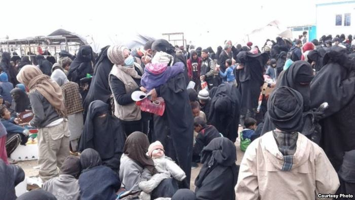 Women and children arrive at a reception area at al-Hol camp in northeast Syr