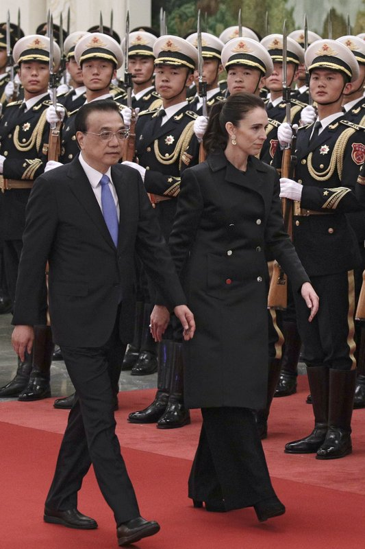 New Zealand Prime Minister Jacinda Ardern, right, and Chinese Premier Li Keqiang review an honor guard during a welcome ceremony at the Great Hall of the People in Beijing, Monday, April 1, 2019. (AP Photo/Andy Wong)