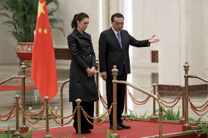 New Zealand Prime Minister Jacinda Ardern, left, is shown the way by Chinese Premier Li Keqiang on stage during a welcome ceremony at the Great Hall of the People in Beijing, Monday, April 1, 2019. (AP Photo/Andy Wong)