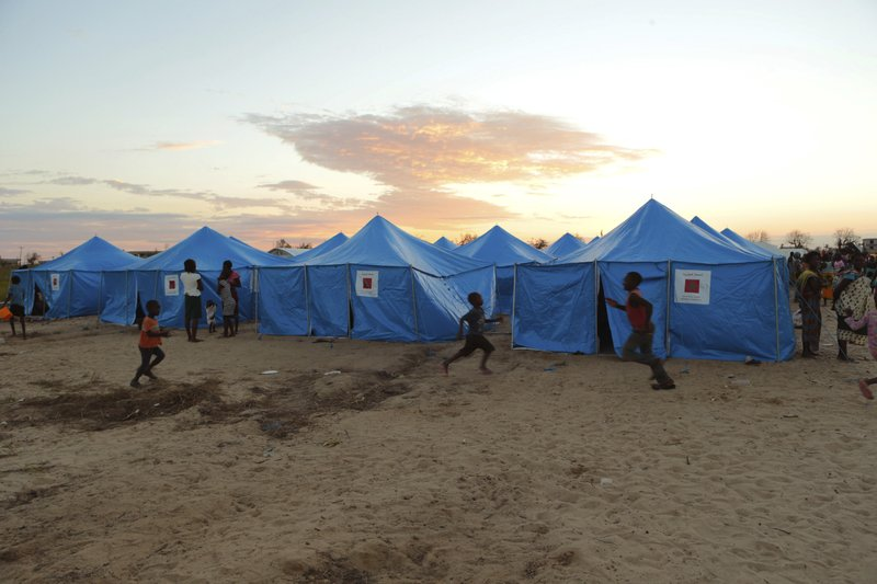 Women and children are outside a displacement camp in Beira, Mozambique, Sunday, March, 31, 2019. Mozambican authorities say the number of cholera cases among cyclone survivors has risen to 271. (AP Photo/Tsvangirayi Mukwazhi)