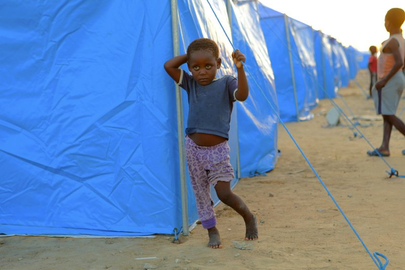 A young boy is seen outside a displacement camp for survivors of Cyclone Idai in Beira, Mozambique, Sunday, March, 31, 2019. (AP Photo/Tsvangirayi Mukwazhi)