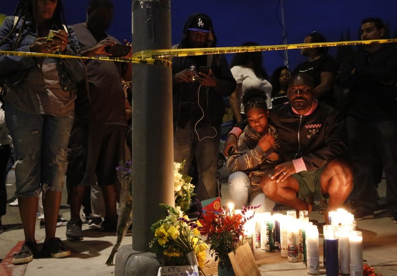 Haitian-French actor Jimmy Jean-Louis and his daughter Jasmin, 16, gather around candles set up across from the clothing store of rapper Nipsey Hussle in Los Angeles, Sunday, March 31, 2019. (AP Photo/Damian Dovarganes)