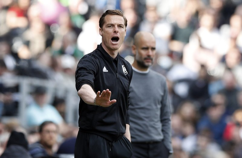 Fulham manager Scott Parker gestures, with Manchester City coach Pep Guardiola in the background, during the English Premier League soccer match between Fulham and Manchester City at Craven Cottage stadium in London, Saturday, March 30, 2019. (AP Photo/Alastair Grant)