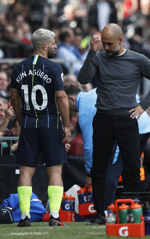 Manchester City's Sergio Aguero talks with Manchester City coach Pep Guardiola after getting injured and being substituted during the English Premier League soccer match between Fulham and Manchester City at Craven Cottage stadium in London, Saturday, March 30, 2019. (AP Photo/Alastair Grant)