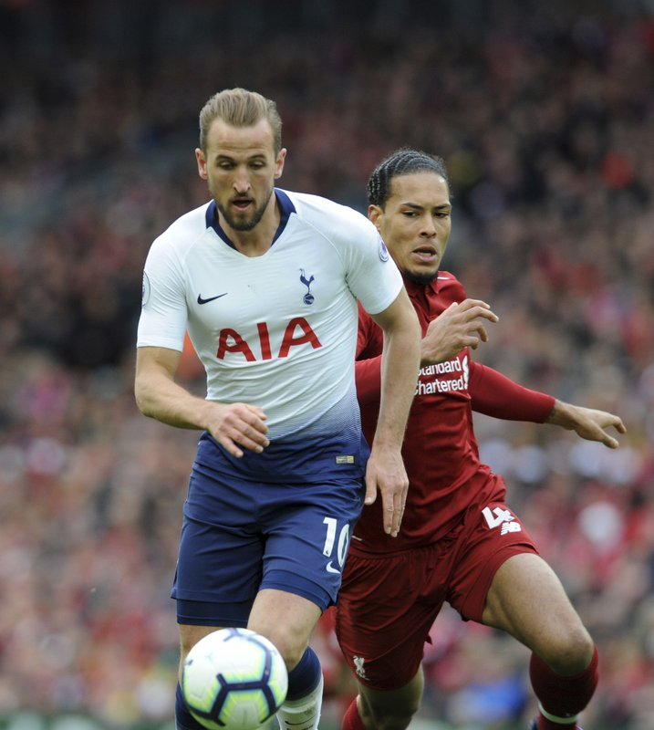 Tottenham's Harry Kane, left, and Liverpool's Virgil van Dijk run for the ball during the English Premier League soccer match between Liverpool and Tottenham Hotspur at Anfield stadium in Liverpool, England, Sunday, March 31, 2019. (AP Photo/Rui Vieira)