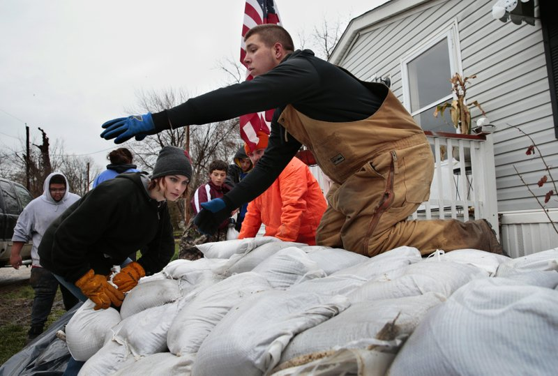 Sky Coleman, left, stacks a sandbag as Tyler Hopkins awaits another as a group of 15 middle and high school students from the nearby city of Louisiana, Mo. (Robert Cohen/St. Louis Post-Dispatch via AP)