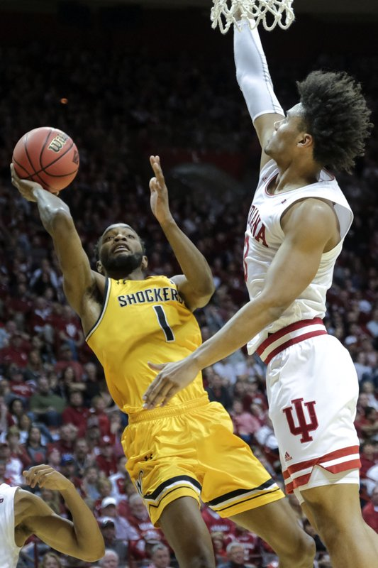 Wichita State forward Markis McDuffie (1) shoots in front of Indiana forward Justin Smith (3) in the first half of an NCAA college basketball game in the third round of the NIT tournament in Bloomington, Ind. (AP Photo/AJ Mast)