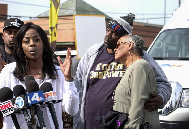 Marcus Woods, second from right, comforts Lita Herron, right, as Denise Francis Woods, second from left, speaks during a news conference near rapper Nipsey Hussle's Marathon Clothing store in Los Angeles, Monday, April 1, 2019. (AP Photo/Ringo H.W. Chiu)