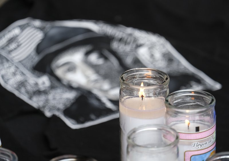 Candles appear at a makeshift memorial for rapper Nipsey Hussle in the parking lot of his Marathon Clothing store in Los Angeles, Monday, April 1, 2019. (AP Photo/Ringo H.W. Chiu)