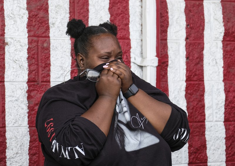 Sydney Flenour cries as she mourns rapper Nipsey Hussle at a makeshift memorial in the parking lot of Hussle's Marathon Clothing store in Los Angeles, Monday, April 1, 2019. (AP Photo/Ringo H.W. Chiu)