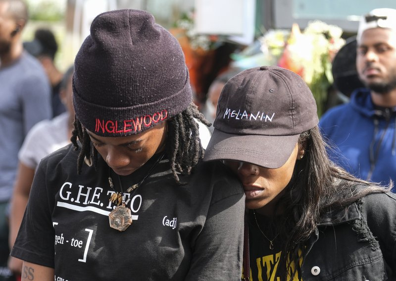 Fans of rapper Nipsey Hussle appear at a makeshift memorial in the parking lot of Hussle's Marathon Clothing store in Los Angeles, Monday, April 1, 2019. (AP Photo/Ringo H.W. Chiu)