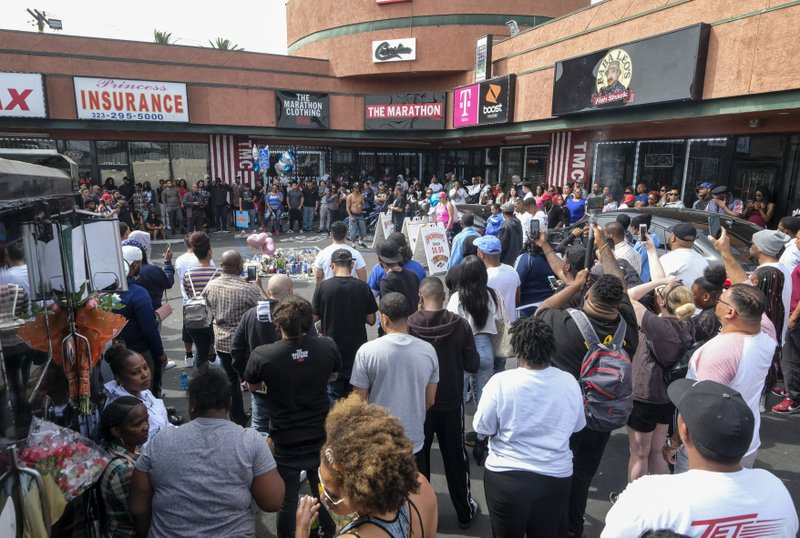 Fans of rapper Nipsey Hussle gather at a makeshift memorial in the parking lot of the Marathon Clothing store in Los Angeles, Monday, April 1, 2019. (AP Photo/Ringo H.W. Chiu)