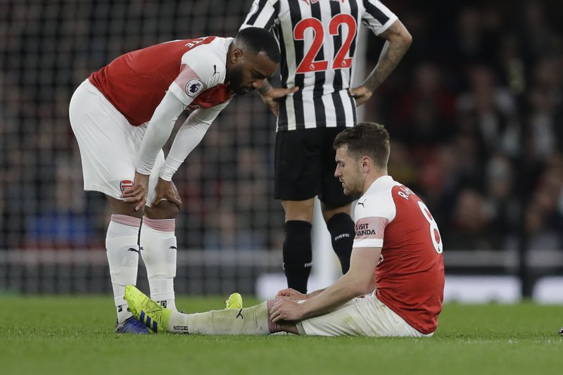 Arsenal's Aaron Ramsey sits injured with Arsenal's Alexandre Lacazette, left, before leaving the game during the English Premier League soccer match between Arsenal and Newcastle United at Emirates stadium in London, Monday, April 1, 2019. (AP Photo/Kirsty Wigglesworth)