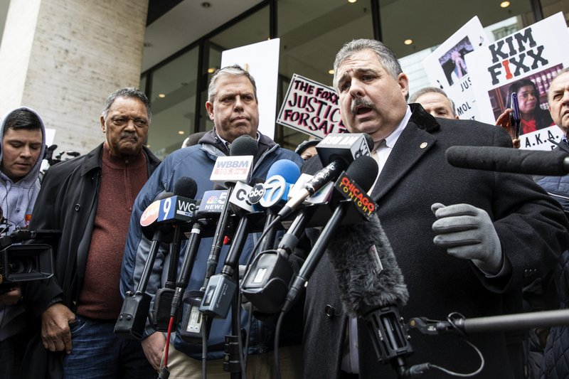 CORRECTS SPEAKER'S LAST NAME TO GRAHAM INSTEAD OF GRAHAMS - Rev. Jesse Jackson, second from left, watches as Fraternal Order of Police President Kevin Graham speaks to reporters during a protest against Cook County State's Attorney Kim Foxx outside the county administration building, Monday, April 1, 2019. (Ashlee Rezin/Chicago Sun-Times via AP)