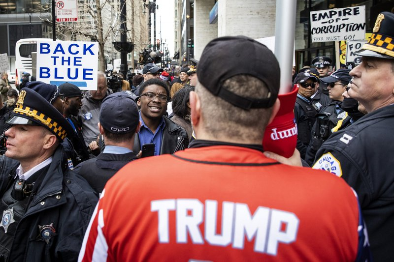 Former mayoral candidate and community activist Ja'Mal Green, background center, verbally spars with Fraternal Order of Police supporters protesting against Cook County State's Attorney Kim Foxx outside the county administration building, Monday, April 1, 2019. (Ashlee Rezin/Chicago Sun-Times via AP)