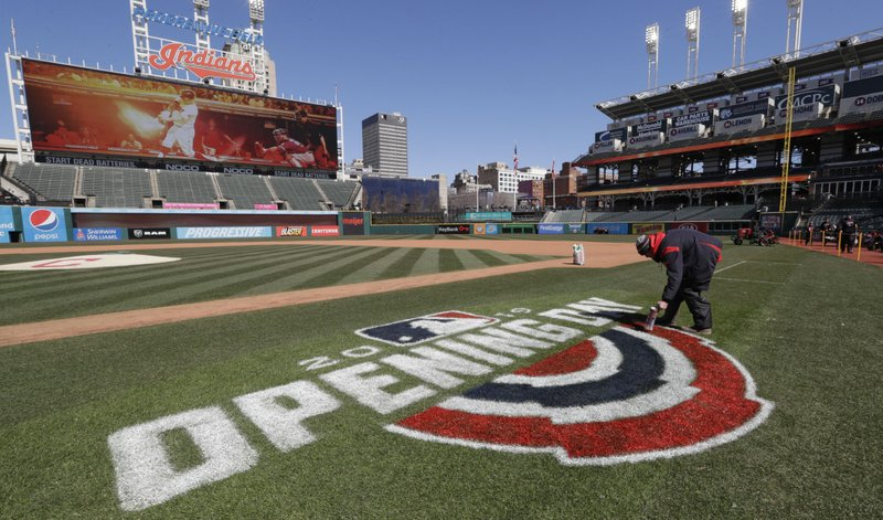 Mathew Gudin paints the opening day signage on the field before the Cleveland Indians play the Chicago White Sox in a baseball game, Monday, April 1, 2019, in Cleveland. (AP Photo/Tony Dejak)