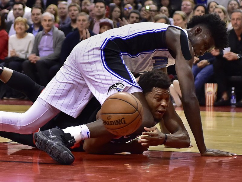 Toronto Raptors guard Kyle Lowry (7) passes the ball from beneath Orlando Magic forward Jonathan Isaac (1) during the first half of an NBA basketball game in Toronto on Monday, April 1, 2019. (Frank Gunn/The Canadian Press via AP)