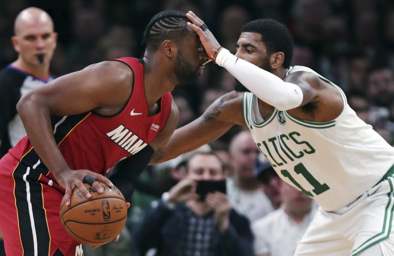 Boston Celtics guard Kyrie Irving (11) blocks Miami Heat guard Dwyane Wade, left, on a drive to the basket during the first quarter of an NBA basketball game in Boston, Monday, April 1, 2019. (AP Photo/Charles Krupa)