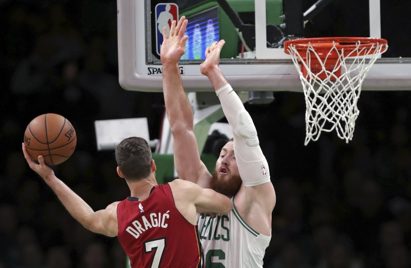 Boston Celtics center Aron Baynes, right,blocks the path of Miami Heat guard Goran Dragic (7) during the first quarter of an NBA basketball game in Boston, Monday, April 1, 2019. (AP Photo/Charles Krupa)
