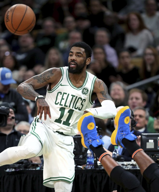 Boston Celtics guard Kyrie Irving (11) passes the ball as Miami Heat guard Dwyane Wade hits the floor during the first quarter of an NBA basketball game in Boston, Monday, April 1, 2019. (AP Photo/Charles Krupa)