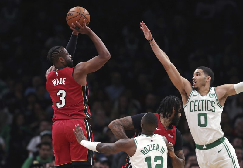 Miami Heat guard Dwyane Wade (3) shoots over Boston Celtics forward Jayson Tatum (0) during the first quarter of an NBA basketball game in Boston, Monday, April 1, 2019. (AP Photo/Charles Krupa)